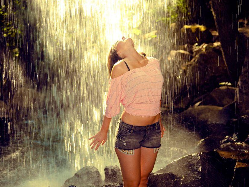 Woman under waterfall photo